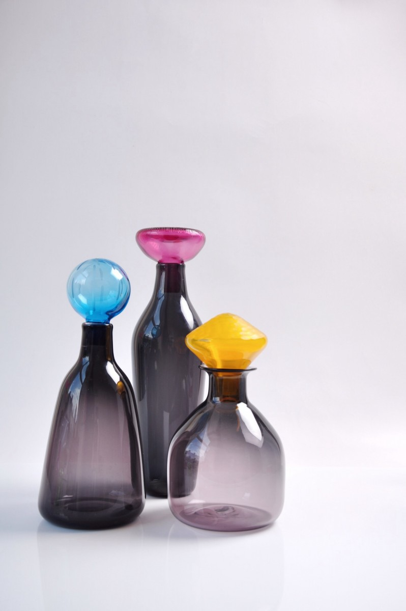 Three grey glass bottles with pink, blue and yellow stoppers