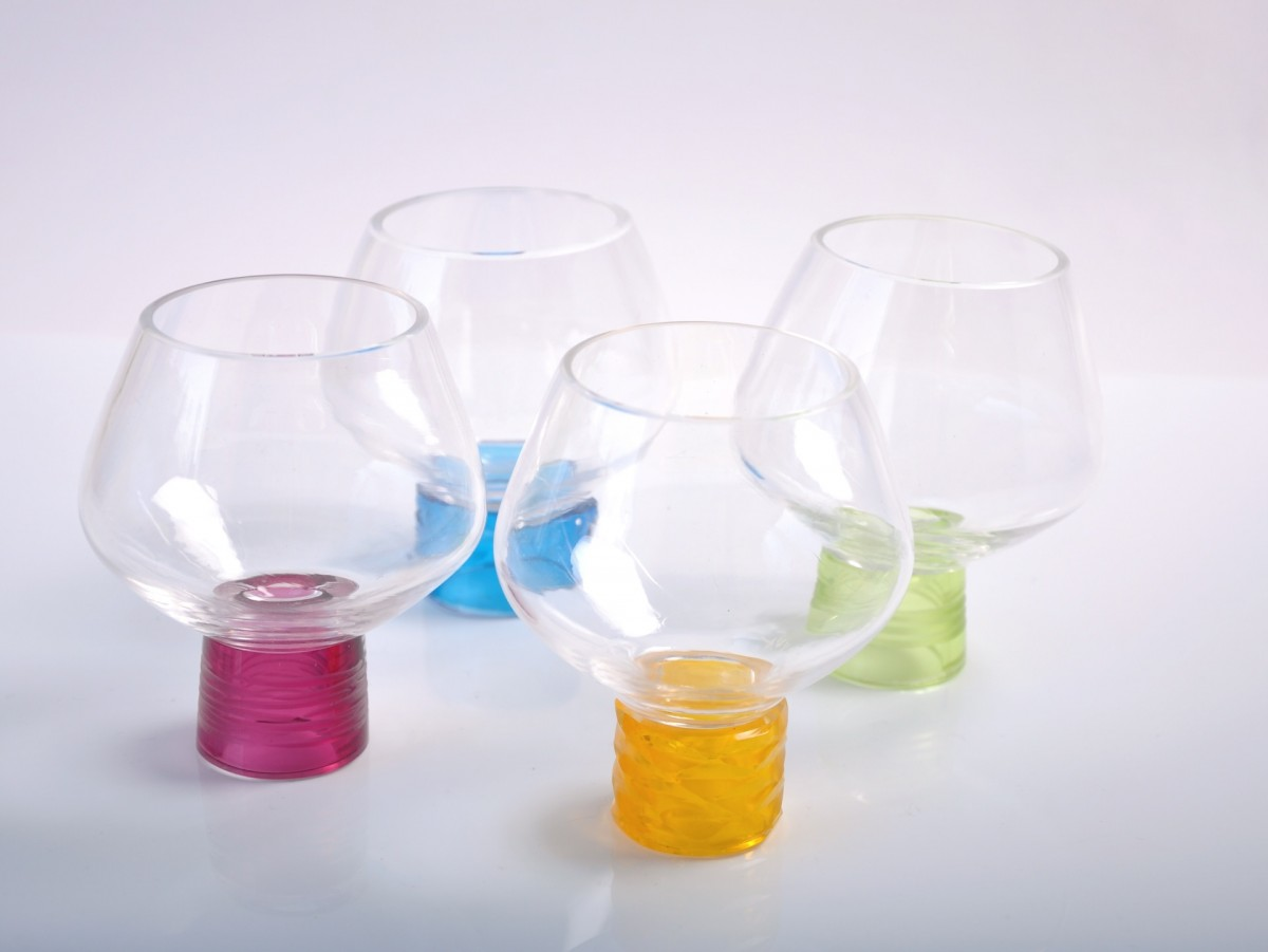 Four clear glass drinking glasses with coloured feet