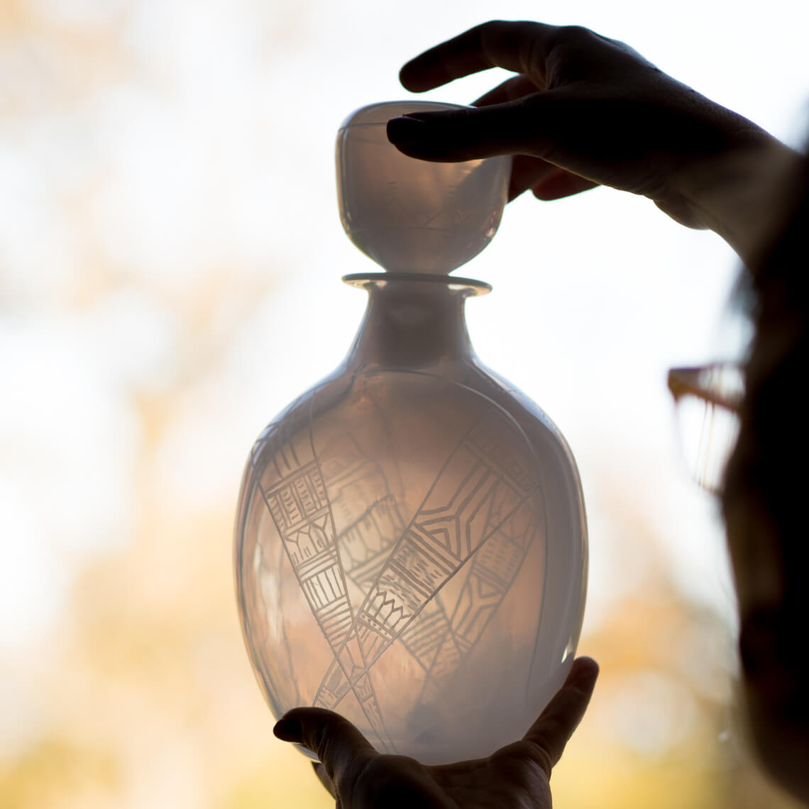 Translucent white glass decanter being held up to the light. The glass is engraved with geometric patterns