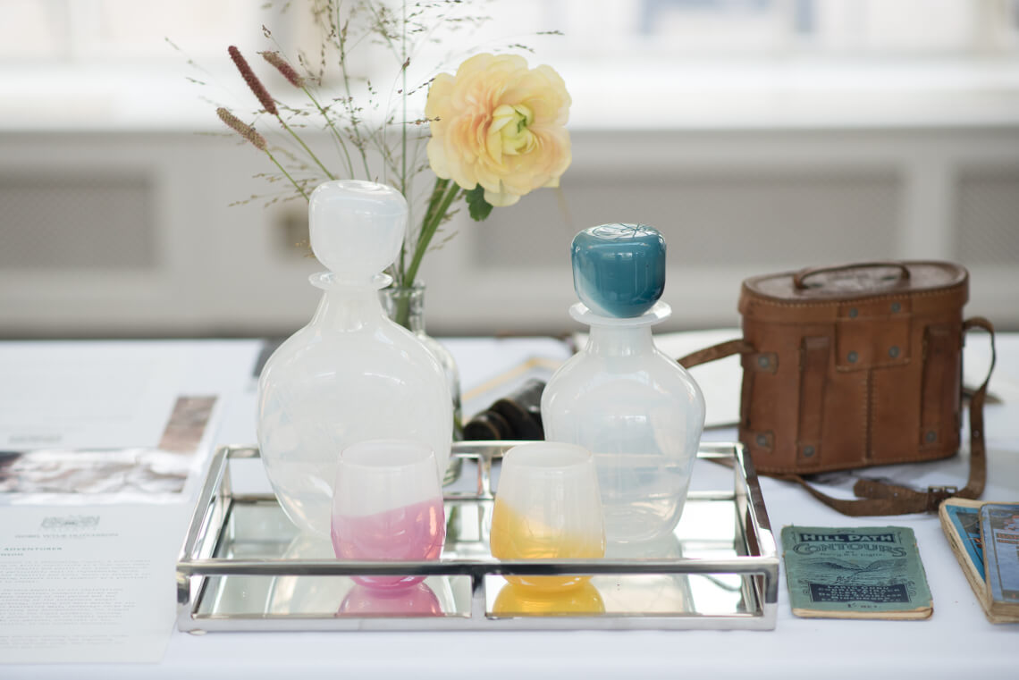 Two glass decanters and glasses sit on a table with historic artefacts