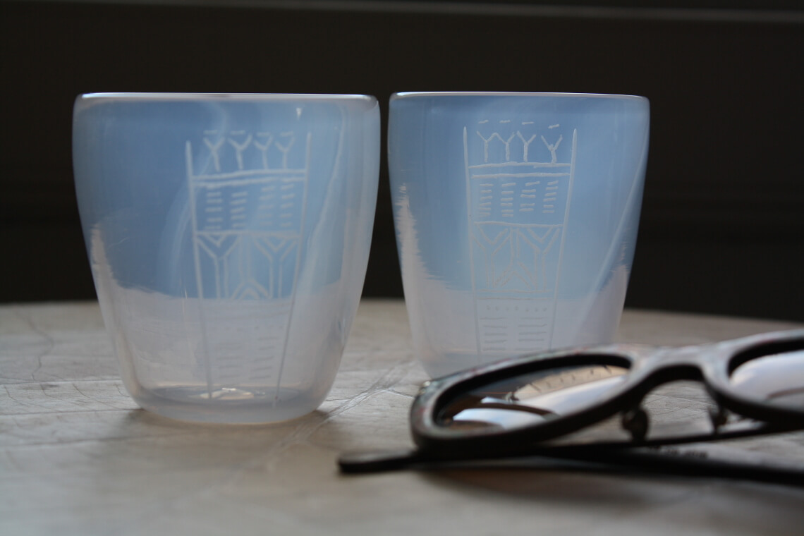 Two translucent white tumblers with geometric engraving sit next to a pair of sunglasses