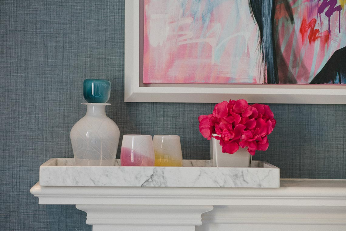 A set of glass decanter and glasses sit on a mantlepiece next to some bright pink flowers and below a brightly coloured painting. The glassware is white, with blue, yellow and pink details and engraved patterns