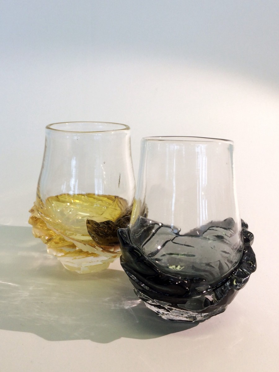 Two whisky glasses with carved grey and amber bases