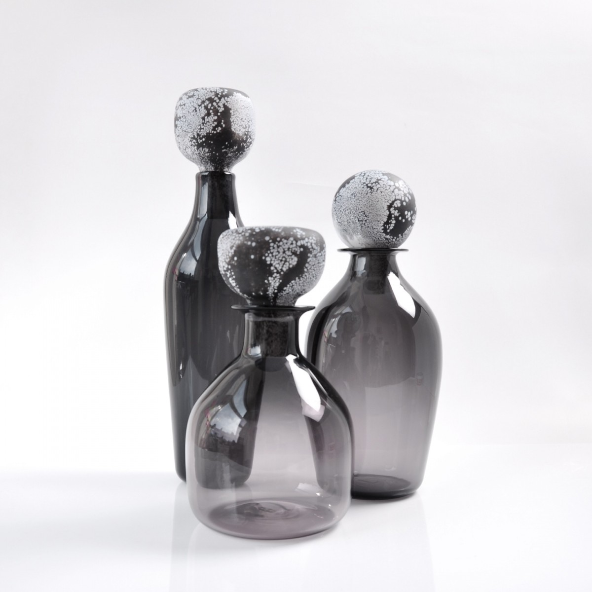 Three grey glass bottles with black and white patterned stoppers