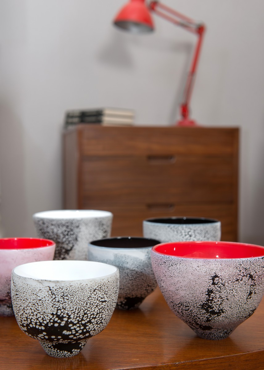 Black white and red glass tea bowls on a table top