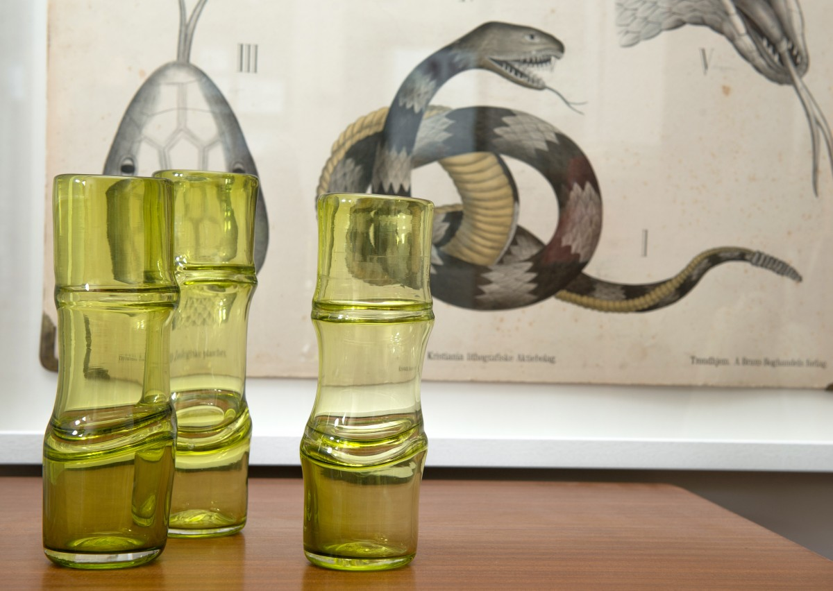 Three green glass vases with bamboo form in front of snake print