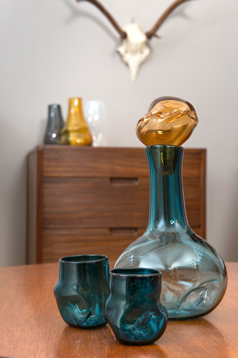 Blue glass decanter and glasses with apricot stopper in front of drawers with glass vases and stag skull