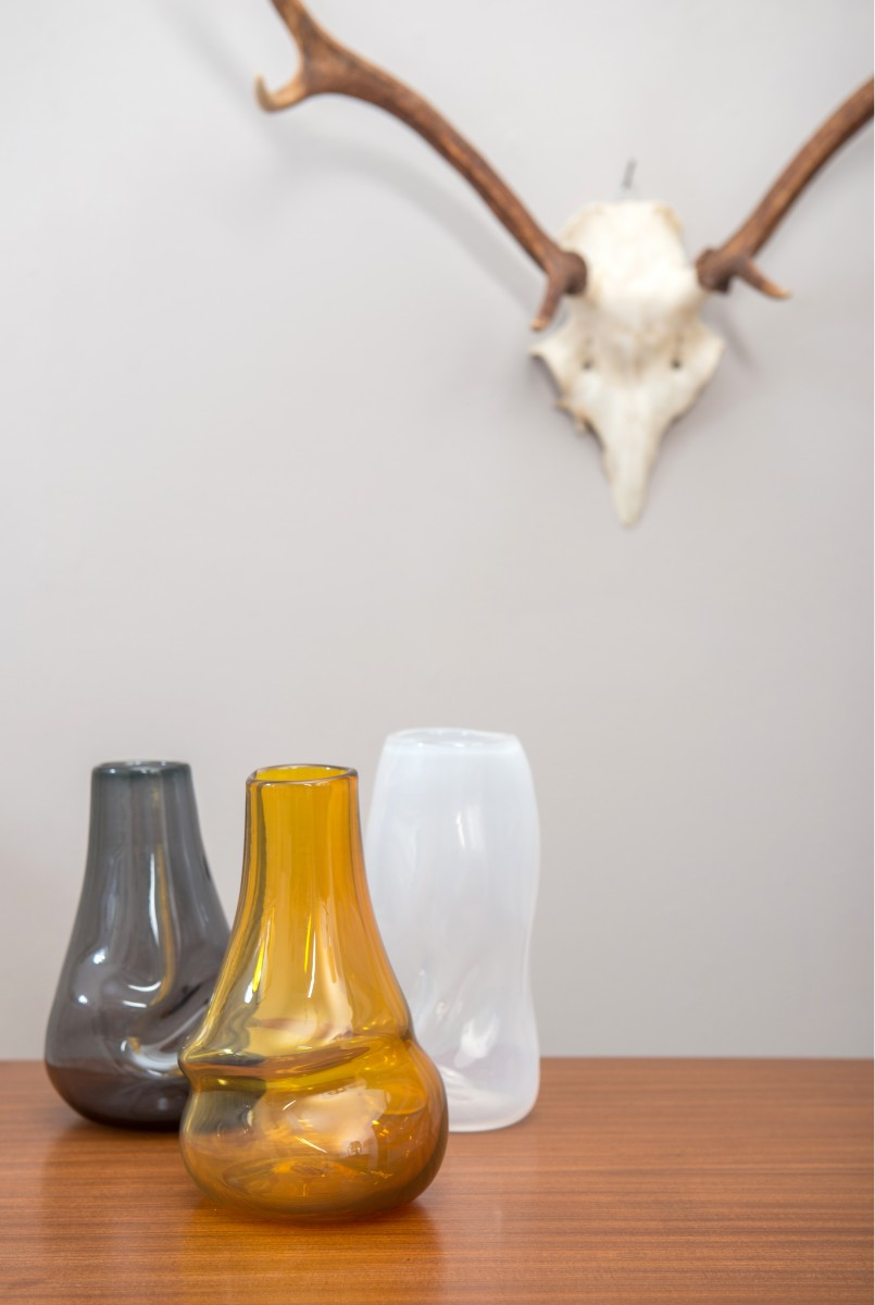 Amber, grey and white glass vases in front of stag skull
