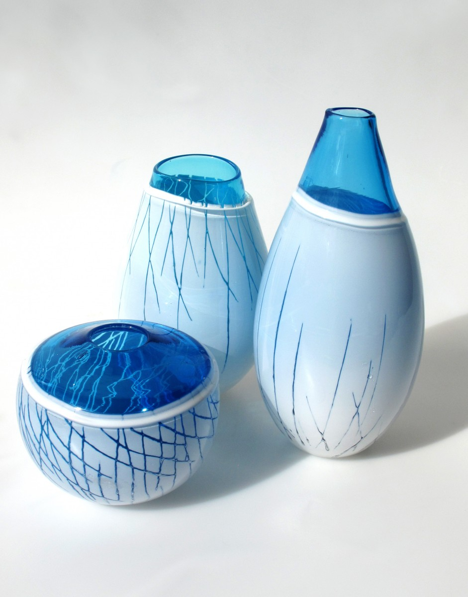 Three blue and white glass vessels with linear patterns