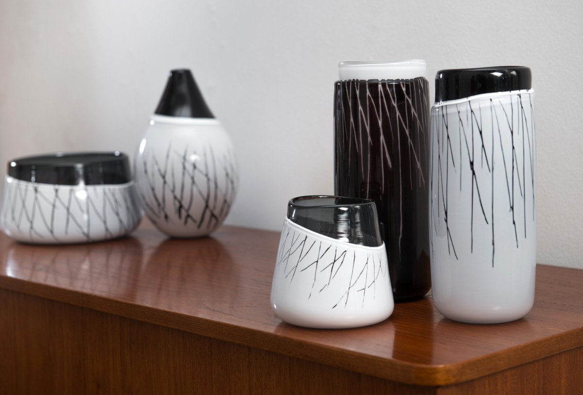 Black and white glass vessels on a sideboard