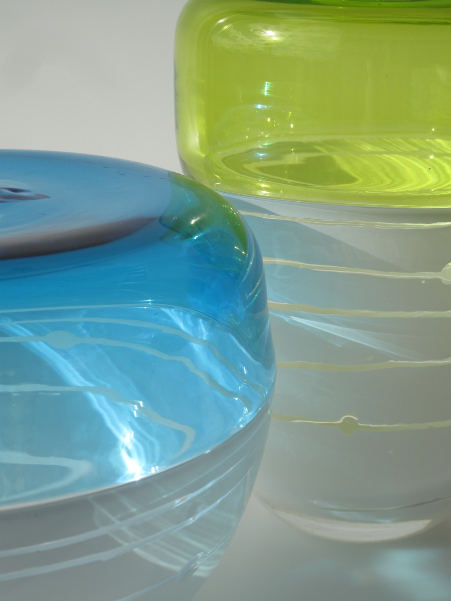 Detail of two glass vessels in green, blue and white with striped engraving