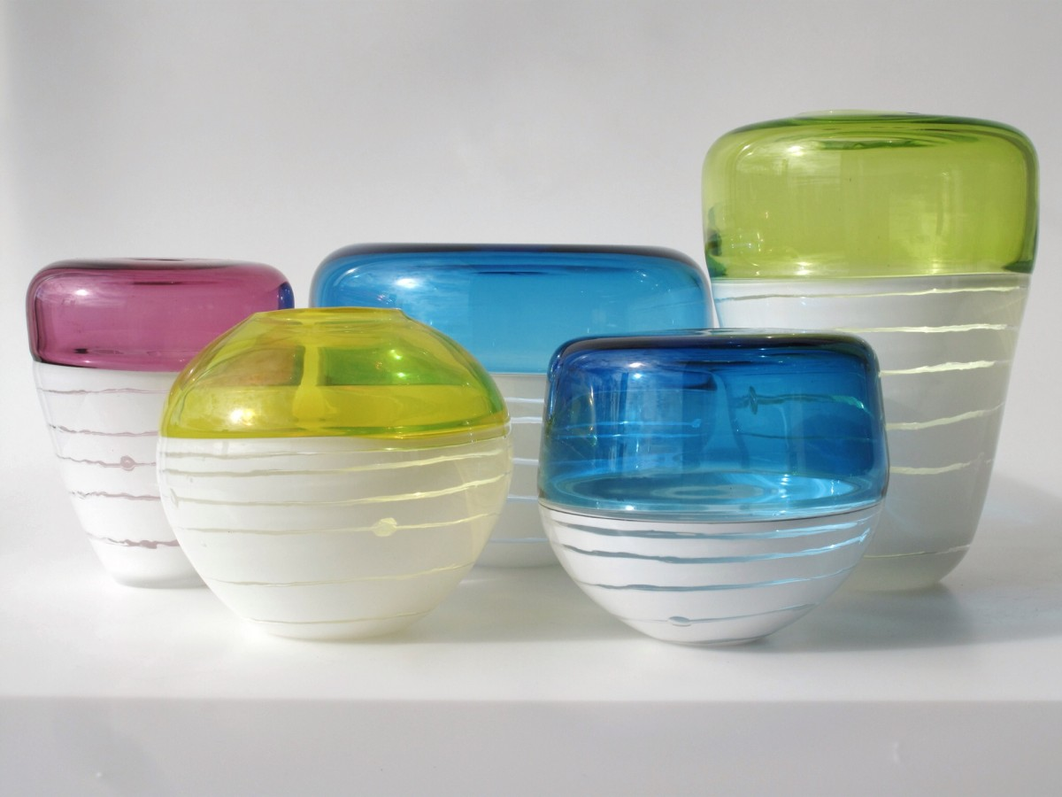 Five glass vessels in blue, yellow, pink and green with white bases