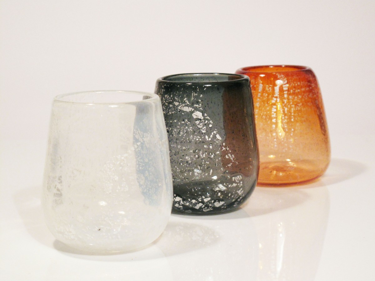 Three glass canlde holders in white, grey and apricot with silver leaf