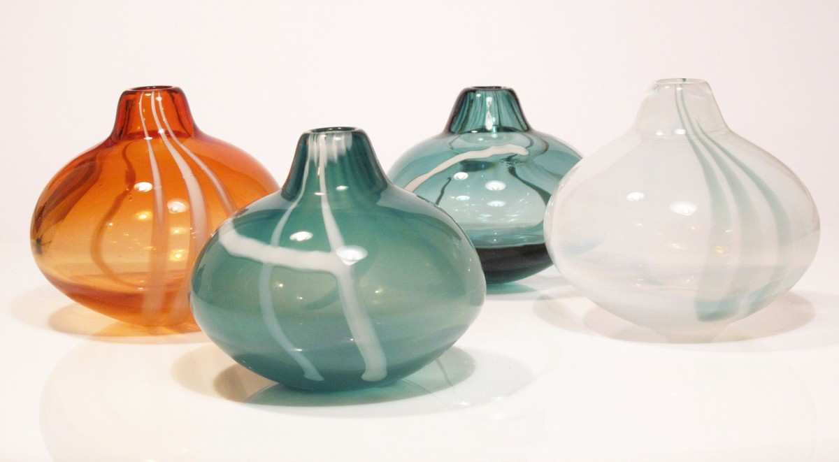 Four small glass vases in apricot,sea green and white