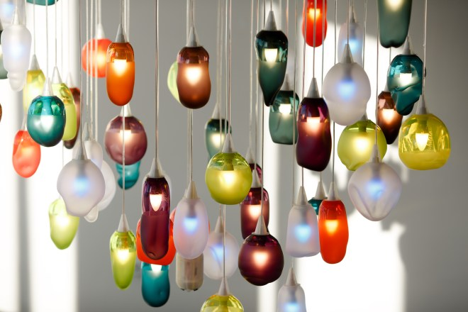 A large group of different coloured glass lights hang in a cluster.