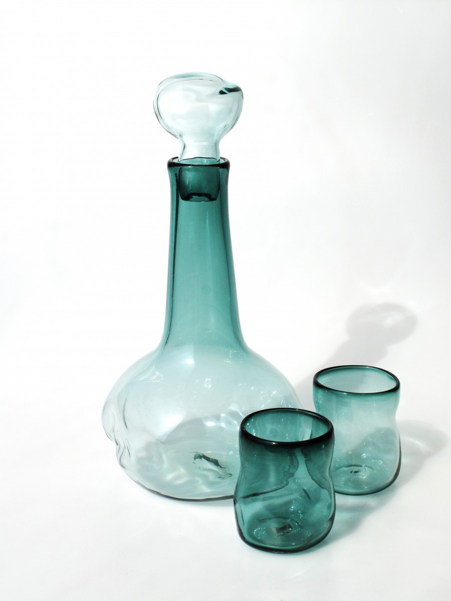 Green transparent glass decanter wnd glasses with collapsed sides.