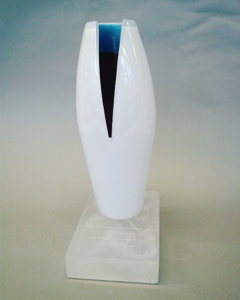 Award object with blown glass top with white exterior and blue/red interior; clear cast glass base.